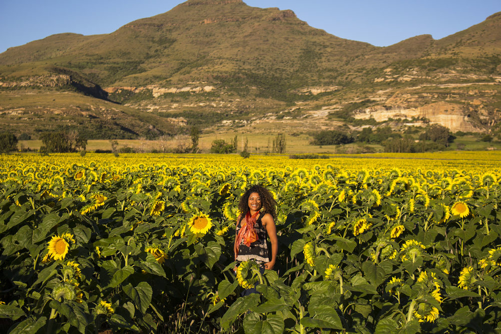 Mzansi Girl walking in sunflower field on My Lime Boots
